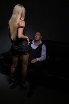 Wunderschöne blonde frau zieht ihr abendkleid aus und steht vor einem eleganten mann, der auf dem sofa sitzt, foto auf dunkler oberfläche