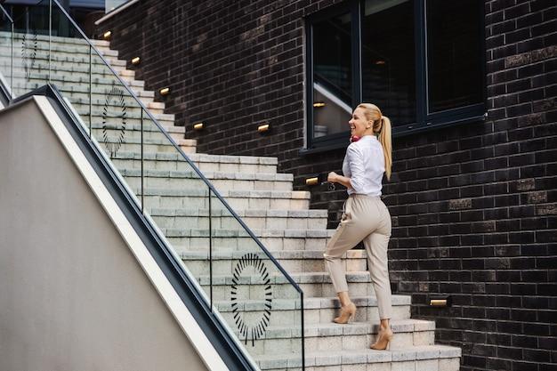 Wunderschöne blonde lächelnde modische dame, die die treppe hinaufsteigt und am telefon spricht.