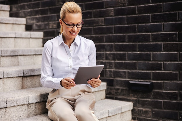 Wunderschöne blonde modische lächelnde geschäftsfrau, die draußen auf der treppe sitzt und tablette verwendet.