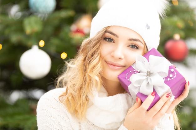 Wunderschöne blonde teenager halten weihnachtsgeschenk nah an ihre wange.