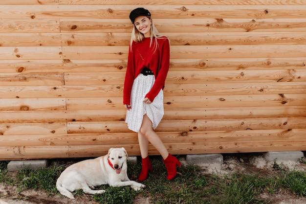 Wunderschöne blondine im weißen kleid und im roten pullover, der auf der holzwand aufwirft. schönes mädchen, das sich gut und glücklich mit ihrem hund im freien fühlt.