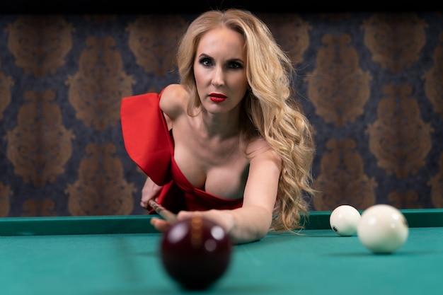 Wunderschöne blondine zielt mit einem hölzernen stichwort auf den ball auf dem billardtisch