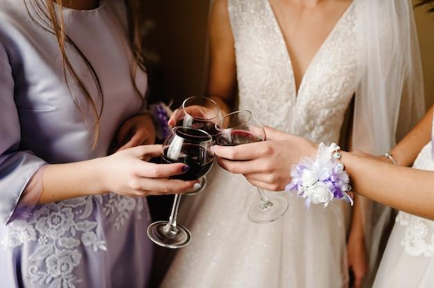 Wunderschöne braut und brautjungfern, die mit wein anstoßen und spaß am hochzeitsmorgen haben. hände halten stilvolle gläser mit getränken und klirren.