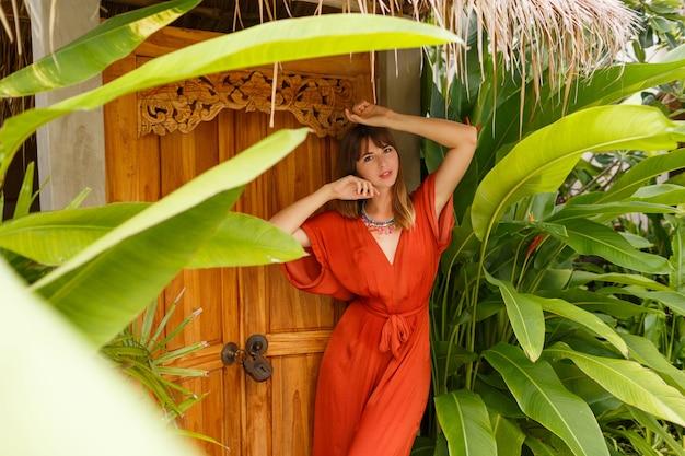 Wunderschöne brünette frau im stilvollen sommeroutfit, das urlaub im luxusresort genießt. exotischer garten mit tropischen pflanzen.