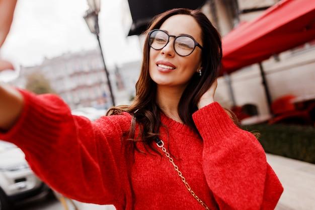 Wunderschöne brünette frau mit perfektem lächeln, das selbstporträt macht. trägt einen roten strickpullover. frühlingsmode