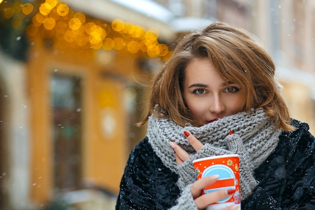 Wunderschöne brünette frau trägt grauen schal und warmen mantel trinkt kaffee während des stadtspaziergangs. freiraum