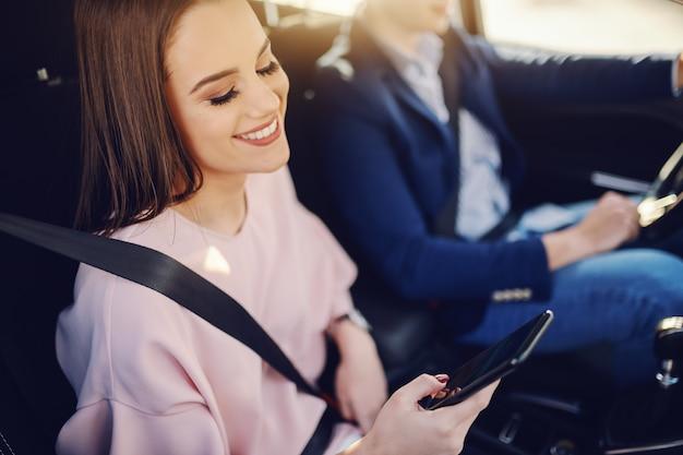 Wunderschöne brünette mit zahnigem lächeln, elegant gekleidet im auto sitzen und smartphone verwenden, während ihr freund im hintergrund fährt.