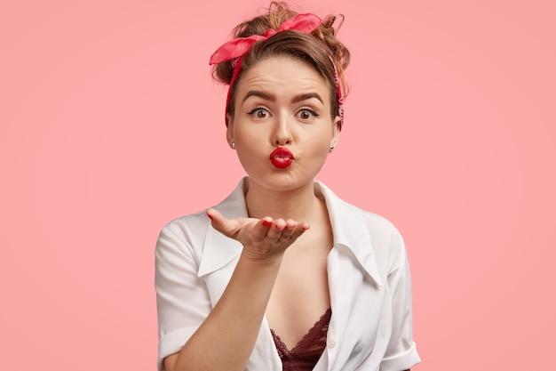 Wunderschöne dame mit make-up, lippen mit rotem lippenstift bemalt, bläst airkiss in die kamera, trägt stilvolles stirnband, verabschiedet sich von freund auf distanz
