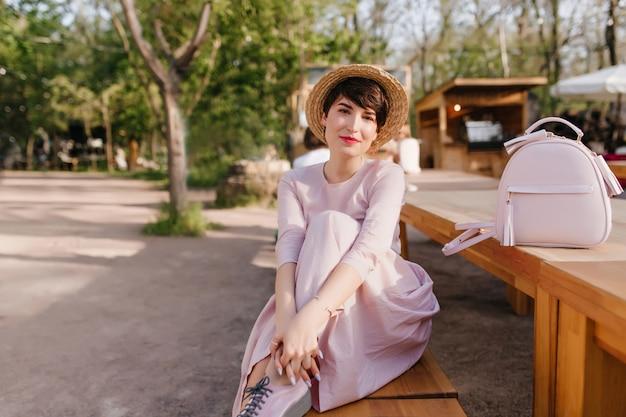 Wunderschöne dame mit trendiger frisur, die auf bank ruht und ihr bein umarmt