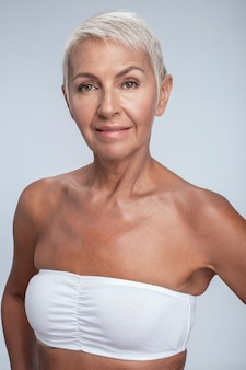 Wunderschöne dame mittleren alters posiert mit weißem bh