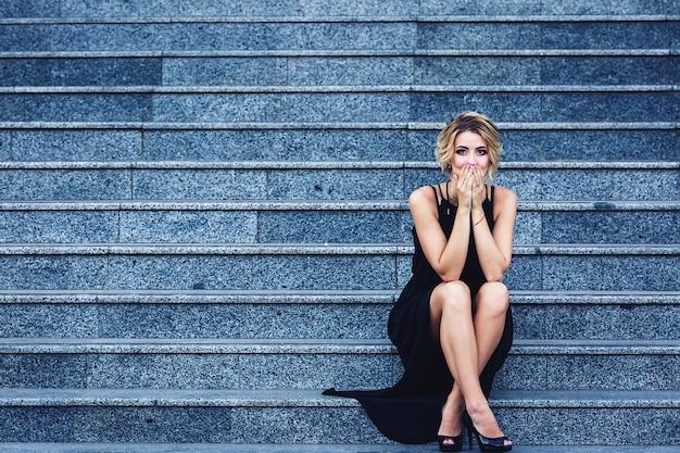 Wunderschöne elegante frau in einem schwarzen kleid sitzt auf der treppe und schließt überrascht den mund.