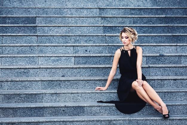 Wunderschöne elegante frau in einem schwarzen kleid sitzt auf der treppe und wartet nachdenklich.