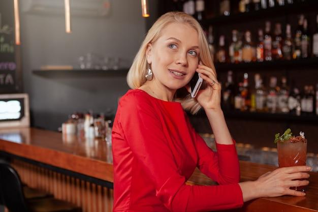 Wunderschöne elegante frau mit smartphone im nachtclub, kopierraum. attraktive frau, die jemanden anruft, der ihr handy an der bar benutzt