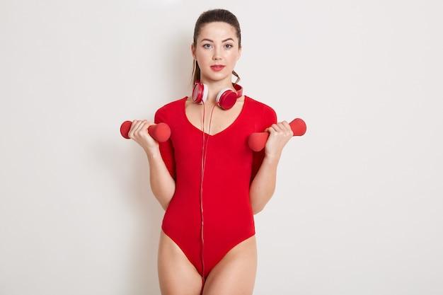 Wunderschöne erwachsene sportfrau, die fitness mit hanteln tut, die über weißer wand lokalisiert werden, entzückendes mädchen, das im verein mit kopfhörern um hals ausarbeitet ,. sportkonzept.