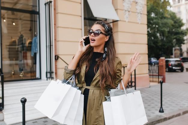 Wunderschöne fashionista-frau, die nach dem einkaufen mit freund am telefon spricht