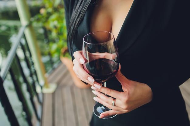 Wunderschöne figürliche brünette frau mit üppigen locken auf dem balkon in einem abendlichen satinkleid.