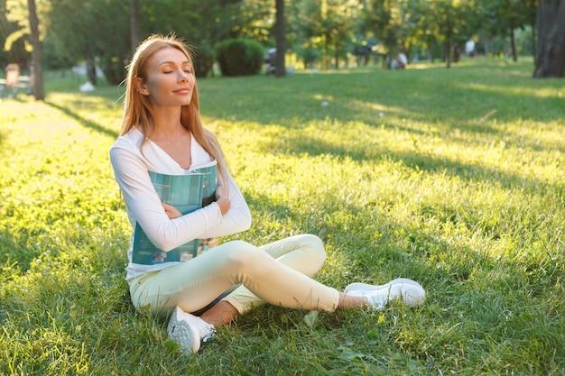 Wunderschöne frau, die frische luft atmet und auf dem gras im park sitzt