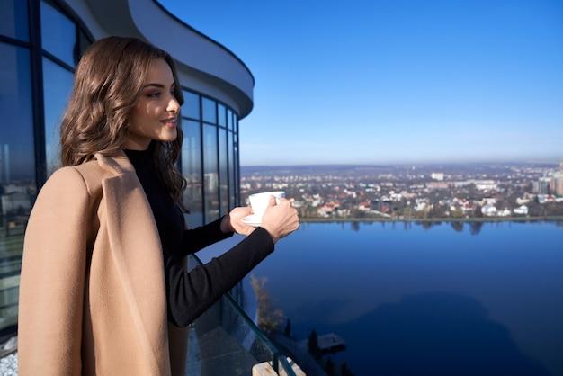 Wunderschöne frau, die kaffee trinkt, während sie auf balkon steht