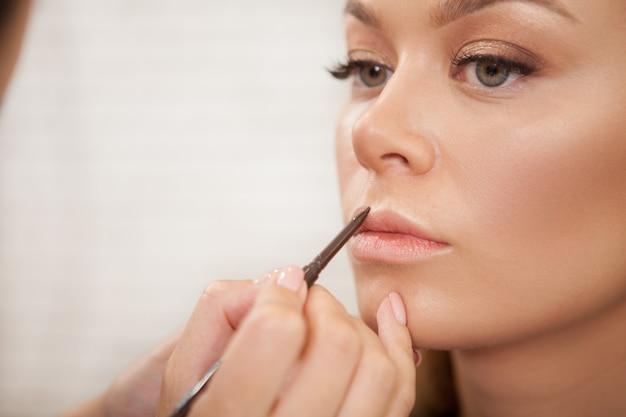 Wunderschöne frau, die professionelles make-up bekommt