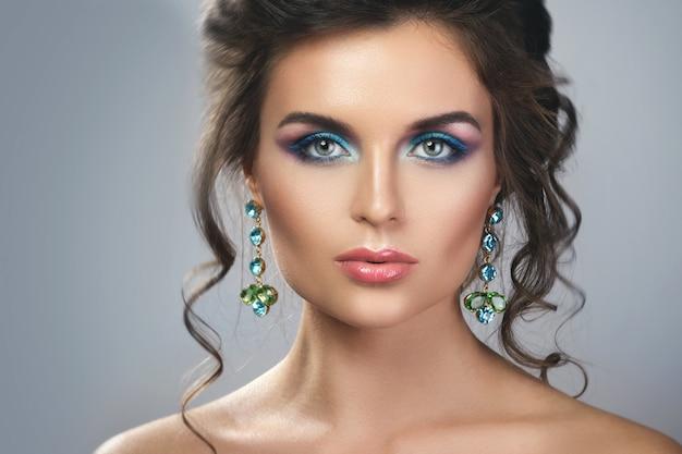 Wunderschöne frau, die schöne teure ohrringe mit juwelen trägt