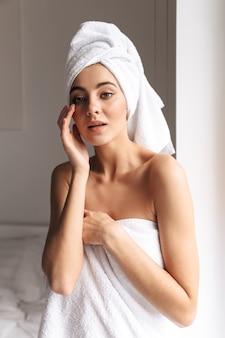 Wunderschöne frau, die weißes handtuch trägt, während sie nach der dusche in der wohnung im badezimmer steht