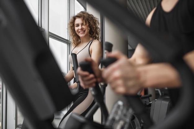 Wunderschöne frau im fitnessstudio, die sport macht