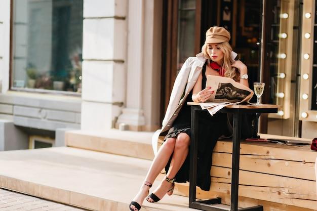 Wunderschöne frau im schwarzen kleid, das im straßencafé ruht und zeitung liest. elegantes mädchen im braunen mantel und im hut, die am tisch mit glas champagner und wartendem freund sitzen.