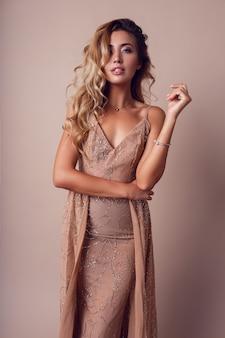Wunderschöne frau mit blondem gewelltem haar, das elegantes beige kleid trägt