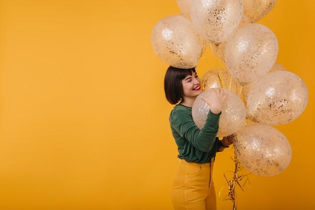 Wunderschöne frau mit braunen haaren, die mit funkelnden luftballons aufwirft. schönes mädchen mit trendigem haarschnitt, das nach der geburtstagsfeier lacht.