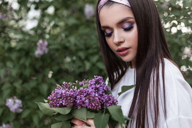 Wunderschöne frau mit farb-make-up mit modischem bandana in weißem, stilvollem hemd mit blumenstraußflieder genießen den frühling auf grünem hintergrundlaub im park. glamour portrait wunderschönes mädchen mit lila blumen.