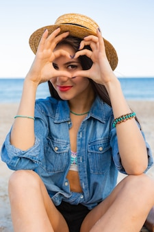 Wunderschöne frau mit hellbraunem körper, vollen roten lippen und l langen beinen, die auf dem tropischen sonnigen strand aufwerfen. tragen von crop top, shorts und strohhut.