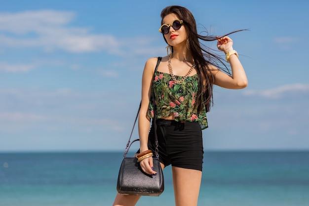 Wunderschöne frau mit langen glatten haaren, die an einem erstaunlichen tropischen strand posng.