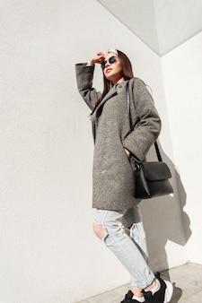 Wunderschöne frau mit modischem bandana in trendigem mantel in jeans in schwarzen turnschuhen mit handtasche in sonnenbrille steht in der nähe des weißen gebäudes und genießt helles sonnenlicht. modisches mädchen in jugendkleidung in der straße