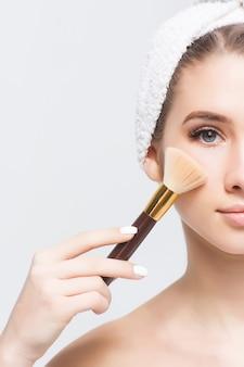 Wunderschöne frau mit natürlichem make-up, die einen pinsel im gesicht hält