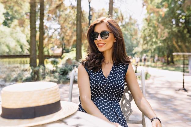 Wunderschöne frau mit schönen haaren und charmantem lächeln sitzt in der sommercafeteria im sonnenlicht. sie trägt ein hübsches sommerkleid und eine schwarze sonnenbrille.