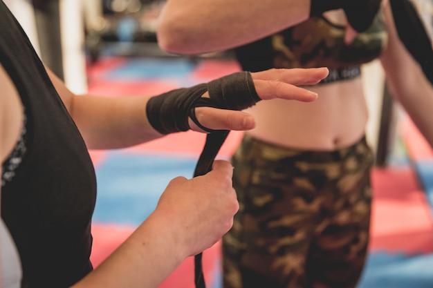 Wunderschöne frau, mma kämpfer im fitnessstudio während des trainings. vorbereitung auf ein hartes käfig-match