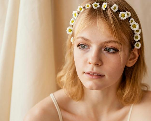 Wunderschöne frau posiert beim tragen einer krone der zarten frühlingsblumen