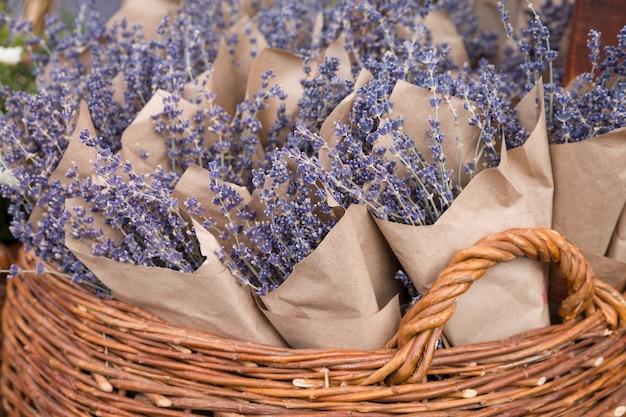 Wunderschöne frische lavendelblüten in kraftpapier im korb auf dem straßenmarkt