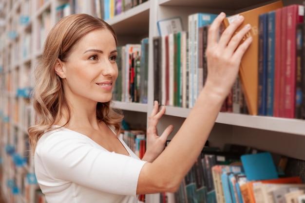 Wunderschöne fröhliche frau, die ein buch aus dem regal in der bibliothek nimmt