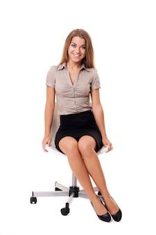 Wunderschöne geschäftsfrau, die auf einem stuhl sitzt