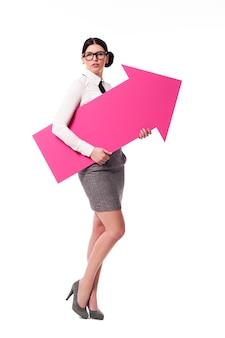 Wunderschöne geschäftsfrau, die rosa pfeilzeichen hält