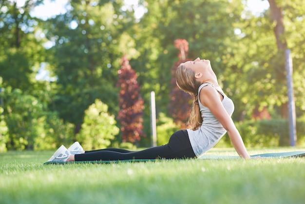Wunderschöne gesunde frau der gesunden passform, die das strecken im freien am park fitness-leichtathletik-sport-sport-lifestyle-morgen-trainingskonzept tut.