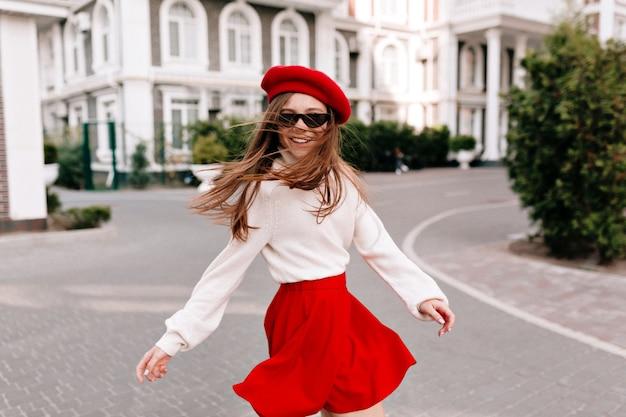 Wunderschöne glückliche frau mit langen haaren gekleidet roten rock und rote baskenmütze drehen sich um
