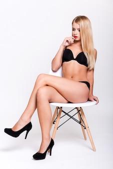 Wunderschöne göttin. attraktive junge frau in schwarzen bh-dessous und high heels
