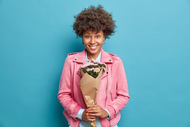 Wunderschöne hübsche afroamerikanische frau mit lockigem haar hält blumenstrauß, der bestem freund im urlaub gratulieren soll, hat festliche fröhliche stimmung trägt rosa jacke, die auf blauer studiowand isoliert wird