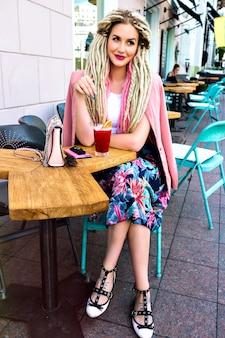 Wunderschöne hübsche elegante frau, die auf terrasse im stadtcafé aufwirft, leckeren cocktail trinkt, trendige helle kleidung, reisen in der europäischen stadt.
