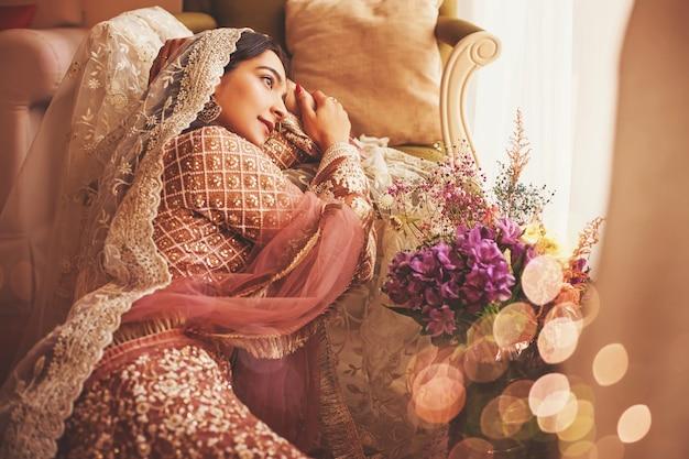 Wunderschöne indische braut im vintage-stil, die in einem luxushotel sitzt?