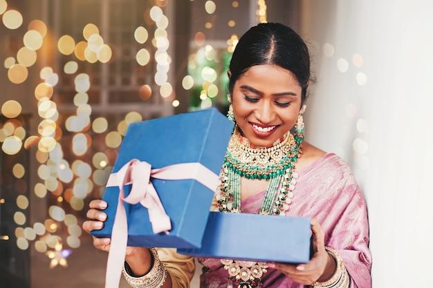 Wunderschöne indische frau in traditionellem schmuck, die ein geschenk öffnet