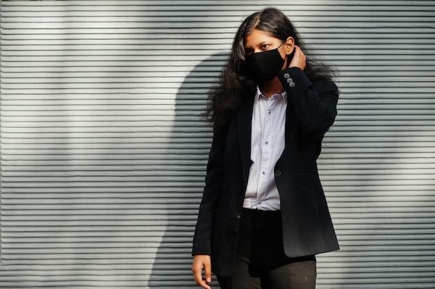 Wunderschöne indische frau tragen formale und schwarze gesichtsmaske, die während der koviden pandämie gegen wand aufwirft.