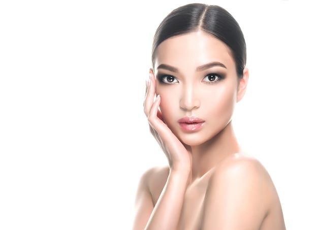 Wunderschöne junge asiatische schwarzhaarige frau mit sauberer frischer haut und zartem make-up berührt das gesicht